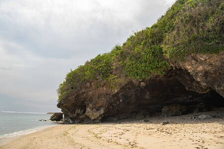 Rocky cliff in deserted beach on island in ocean
