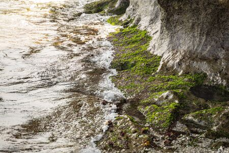 Ocean is bouncing against stones with moss on island