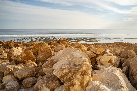 Stones under sun on ocean shore of deserted island