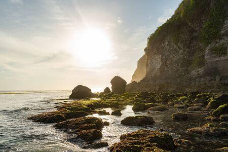 Sun is shining on wild beach with stones under cliff Reklamní fotografie