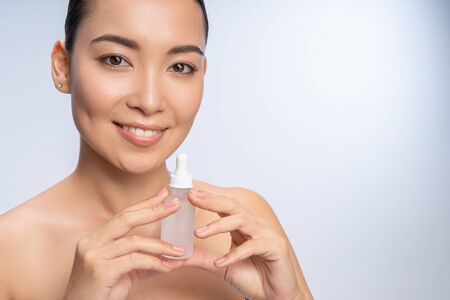 New cosmetics. Cheerful Asian girl keeping smile on her face, holding bottle with serum