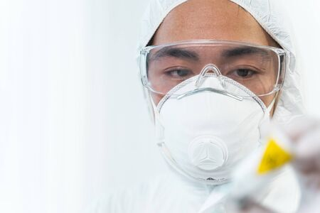 Time to work. Attentive international researcher having mask on face while testing new vaccine