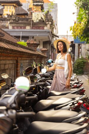 Female is choosing motor bike at parking for travelling in exotic country. Active tourism concept 写真素材