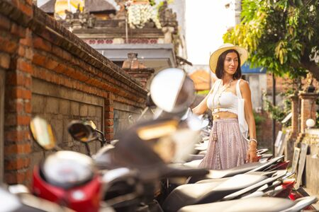 Smiling woman is walking in streets and coming to parking for renting motorbike. Website banner