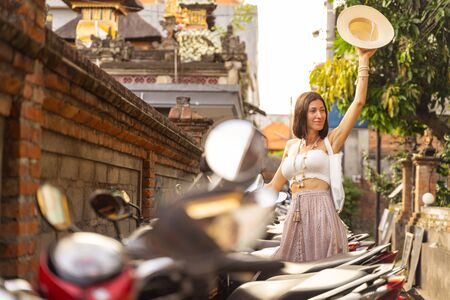 Happy beautiful lady is standing and raisung hat with joy while hiring motorbike. Website banner