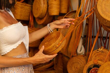 Beautiful female is coming for buying souvenirs and choosing wicker bag of rods and straw