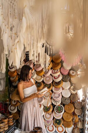 Jolly girl is buying souvenirs of wicker bags in local shop while travelling to exotic country
