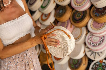Young female is travelling and buying handmade souvenirs in local basketry store. Local market concept