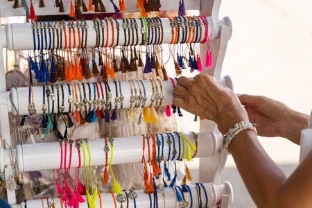 Female tourist is buying souvenirs in local market and choosing colour bracalets with exotic charms