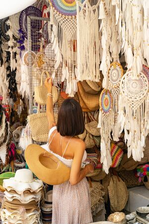 Young woman is strolling among souvenir shops abroad and choosing unique handmade gift. Buying local souvenirs concept 写真素材