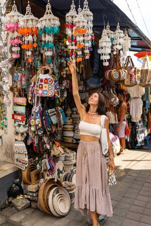 Cheerful young lady is walking in local streets between souvenir shops with handmade charms during her trip