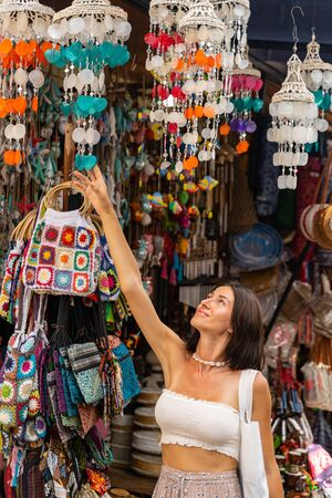Cheerful young lady is travelling abroad and choosing handmade souvenirs while walking in local market. Tourism concept