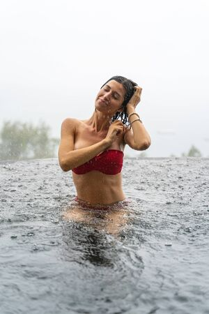 Front view of a joyous female tourist sitting in a swimming pool with her eyes shut