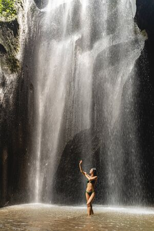 Swim with pleasure. Delighted fitness woman demonstrating her figure while being in water near cave Stockfoto
