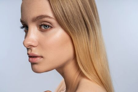 Closeup portrait of a tranquil dreamy pretty Caucasian lady with blonde long hair looking away Reklamní fotografie