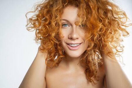 Portrait d'une jeune femme caucasienne gaie touchant ses cheveux roux bouclés avec les deux mains Banque d'images