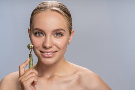 Keep smiling. Cheerful blonde girl using her jade roller while taking care of her skin