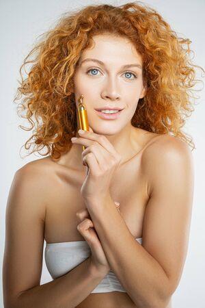 Portrait of a beautiful young Caucasian female massaging her cheek with a golden face massager Stock fotó