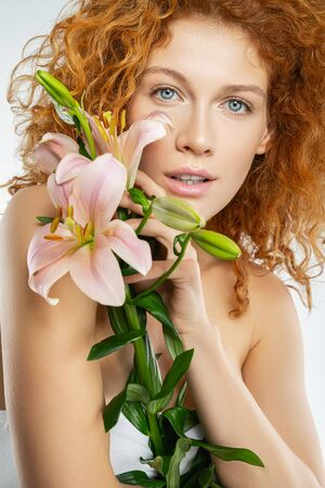 Closeup portrait of a tranquil red-haired pretty woman holding the pink lilies in her hand