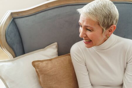 Waist-up portrait of a pleasant senior woman in a sweater laughing heartily on the sofa