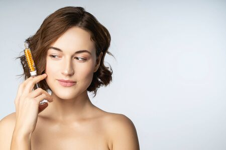 Home salon. Cheerful young female person holding package with serum while going to do lifting procedure