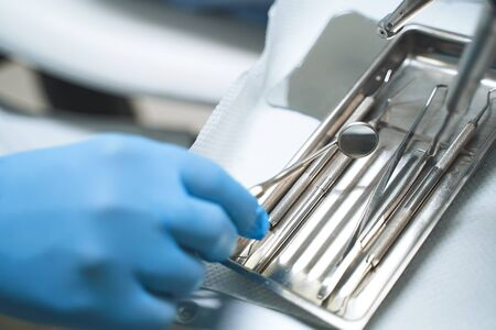 Close up of dentist hand in sterile glove taking dental mirror out of set of instruments for working with patient