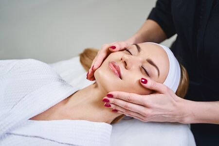 Relaxed young female is resting on couch while cosmetologist massaging her face
