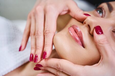 Cheerful young lady is relaxing on couch in beauty salon and having her face massaged by professional Imagens