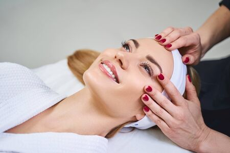 Merry young woman is having good time in salon while having her face massaged by professional
