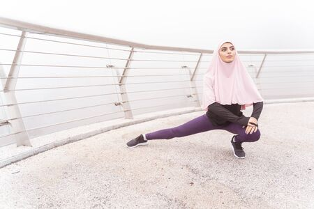 Confident pretty woman in hijab looking away and lunging on the bridge Standard-Bild