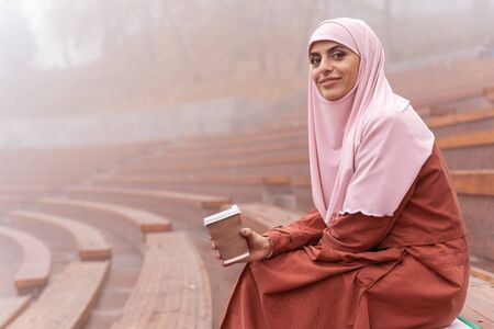Pleased young woman in hijab relaxing on a grandstand with coffee to go. Website banner