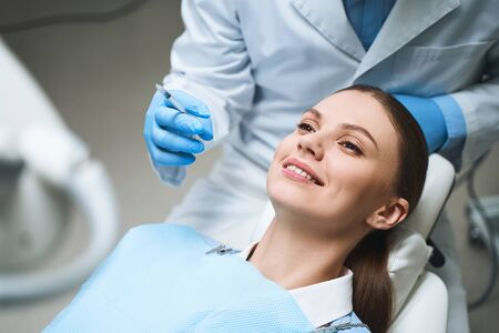 Happy woman is lying in dental chair and preparing for injection before tooth procedure. Website banner