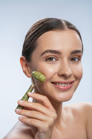Portrait of happy young woman taking care of her skin and doing massage with cosmetology device stock photo