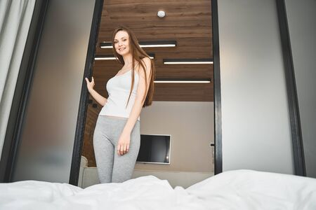 Low angle of a contented slim Caucasian girl in home clothing smiling at the camera
