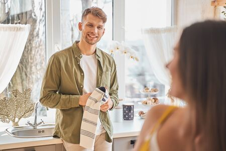 Happy weekend. Positive delighted brunette man keeping smile on his face while looking at his girlfriend
