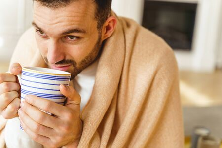 Closeup portrait of a low-spirited man holding a cup of hot beverage with both hands