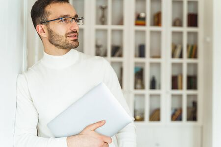 Waist-up portrait of a pleased Caucasian office worker with a computer looking into the distance
