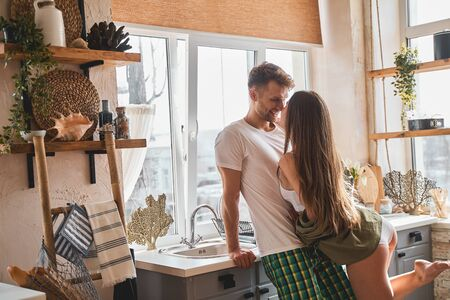 Be positive. Delighted bearded man leaning on furniture while having close communication with his girlfriend