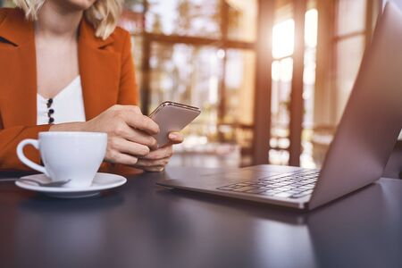Cropped photo of a blonde young female entrepreneur with a cellphone sitting at a desk Stock Photo