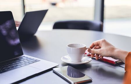 Cropped photo of a young Caucasian business lady with a laptop sitting at an office desk Stock fotó