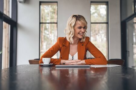 Cheerful elegant Caucasian young business lady with her hands clasped on the desk laughing heartily
