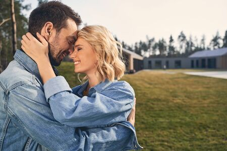 Smiling high-spirited attractive blonde female and her boyfriend in denim jackets hugging each other outside