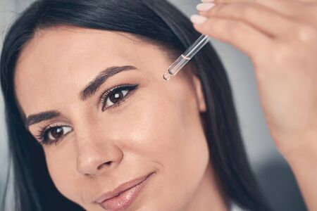 Close up portrait of a woman applying a facial oil to the skin with a pipette
