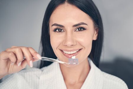 Close up portrait of a girl with a pea-sized amount of toothpaste on the brush smiling at the camera