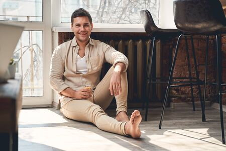 Front view of a high-spirited barefoot handsome male in casual clothes sitting on the floor 免版税图像