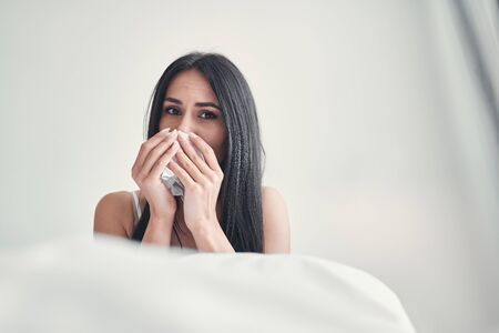 Sad brunette girl wiping her nose while being on self-isolation at home, sitting on the bed
