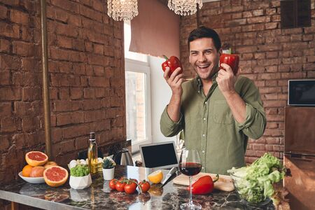 Front view of a handsome high-spirited Caucasian male cook holding bell peppers in his hands