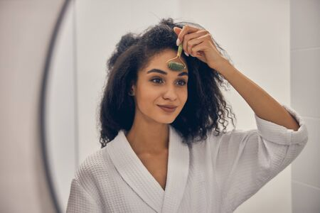 Portrait d'une femme dans un peignoir gaufré massant son front devant le miroir