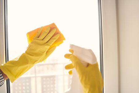 Young woman spending her weekend at home while cleaning windows with special liquid