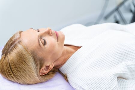 Relaxed middle-aged blonde woman with eyes closed lying on the couch in a dermatologists office